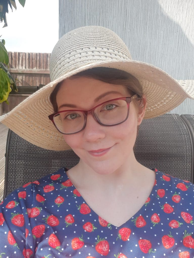 Blogger Anstice Brown in a red and blue strawberry print dress with a sun hat for VE Day