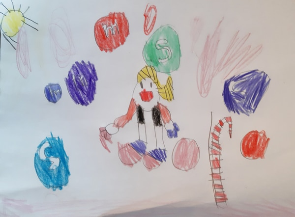 child's drawing of a girl in candyland surrounded by colourful M&Ms and candy canes