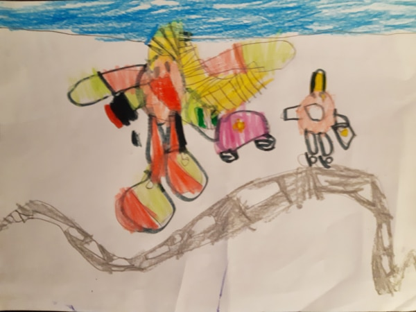 Child's drawing of herself as a superhero, flying over a road full of cars to rescue someone